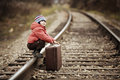 Boy sitting with suitcase near the railway journey a Stock Image