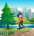 A boy skateboarding near the riverbank illustration of Stock Images