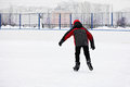 Boy skating rear view on the ice rink alone Royalty Free Stock Photos