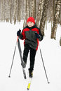 Boy on skis in winter forest raising one ski Royalty Free Stock Photo