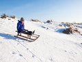Boy sledging small enjoys fast down a snow covered hill Royalty Free Stock Photo