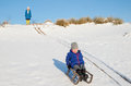 Boy sledging smiling down a snow covered dune with women wathcing in the background Stock Photography