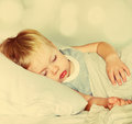 Boy sleeping on a bed toned little with fair hair effect bokeh and Stock Photos