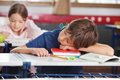 Boy sleeping while girl studying in background elementary at classroom Royalty Free Stock Photos