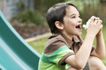 Boy on slide using inhaler in park side view of young Royalty Free Stock Image