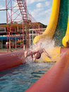 Boy slides down the water slides at background splashing Stock Image
