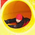 Boy sliding down in tube yellow playground Royalty Free Stock Photo