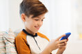 Boy with smartphone texting or playing at home leisure children technology internet communication and people concept smiling Royalty Free Stock Photos