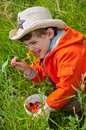 Boy smelling the flower with exhilaration three year old holding a bucket of strawberrys and Stock Image