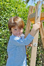 The boy with a smile poses on step ladder charming little in background spring green hedges Royalty Free Stock Image