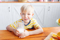 Boy are smiling while having a breakfast in kitchen. Mom is pouring milk into glass Royalty Free Stock Photo
