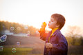 Boy with soap bubbles smiling blowing the on the autumn landscape against sunset Stock Photos
