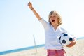 Boy with soccer ball and winning attitude portrait of standing on beach Royalty Free Stock Image