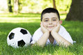 Boy with soccer ball young cute happy lying on grass Royalty Free Stock Image