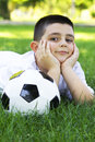 Boy with soccer ball young cute happy lying on grass Stock Images
