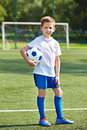 Boy soccer football player with ball on an green grass Royalty Free Stock Photo