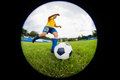 Boy soccer player hits the ball on football field fish eye lens Royalty Free Stock Photos