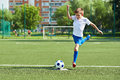 Boy soccer player with jump before kick on ball Royalty Free Stock Photo