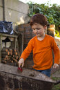 Boy with spade and wheelbarrow a young throwing sand into a a small working in the garden Stock Photo