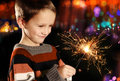 Boy with sparkler young holding burning on festive lights background Stock Image