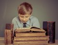 The boy spends time reading old books ancient a a child prodigy Stock Image