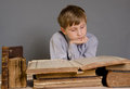 The boy spends time reading old books ancient a a child prodigy Royalty Free Stock Photo