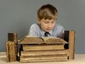 The boy spends time reading old books ancient a a child prodigy Royalty Free Stock Image