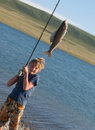 The boy with a spinning catch grayling Royalty Free Stock Photo