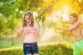 Boy splashing girl with water gun sunny summer garden fun in day back yard Royalty Free Stock Image