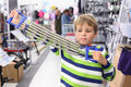 Boy in sports shop tries metal shoulder expander Royalty Free Stock Photo