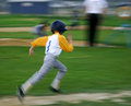 Boy sprints for base young in yellow jersey runs after a hit in baseball game Stock Photos