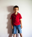 Boy standing against wall dropping shadow Royalty Free Stock Image