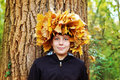 Boy standing in autumn park on a background of trees. At the head of woven wreath of autumn leaves