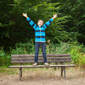 Boy standing on a bench in a forest teenage is his arms up the air he looks very happy Royalty Free Stock Photo