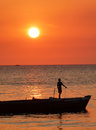 Boy standing on boat silhouetted against a bright orange sunset off zanzibar coast stands in an open the of vivid huge sun still Royalty Free Stock Image