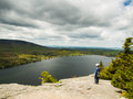 Boy standing on a cliff high above lake Royalty Free Stock Photos