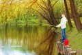 Boy standing and fishing near the pond Royalty Free Stock Photo