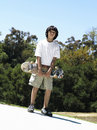 Boy standing in park holding skateboard front view portrait tilt Stock Photos