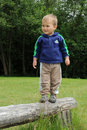 Boy standing on wooden bar Royalty Free Stock Photo