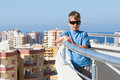 A boy stands on balcony of hotel the the the background the cityscape and skyline Royalty Free Stock Photo