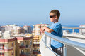 A boy stands on the balcony of hotel and looks into distance background of cityscape and skyline Royalty Free Stock Photography