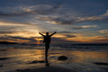 Boy stands on beach with arms outstretched under a dramatic sunset sky Royalty Free Stock Photo