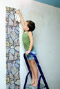 A boy stands on a ladder and glues wallpaper little the stairs smoothes Stock Photo