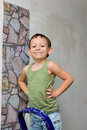 A boy stands on a ladder and glues wallpaper little the stairs smoothes Royalty Free Stock Photography