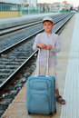 Boy stands on platform of railway with travel bag Royalty Free Stock Images