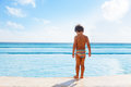 Boy stands on stone boarder of swimming pool Royalty Free Stock Photo