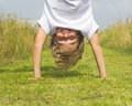 Boy stands upside down a in the summer grass Stock Images