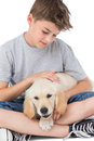 Boy stroking dog over white background loving while sitting Stock Image