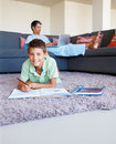 Boy studying on floor with father at the back Royalty Free Stock Photos