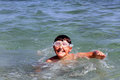 Boy on summer holidays active swimming in the sea water Stock Photos